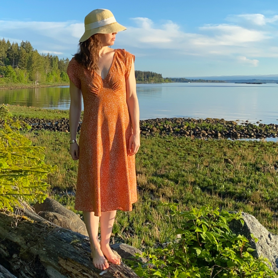 Me standing on a log on the beach with the water behind me, wearing a orange v-neck midi dress with white polka dots and a sun hat