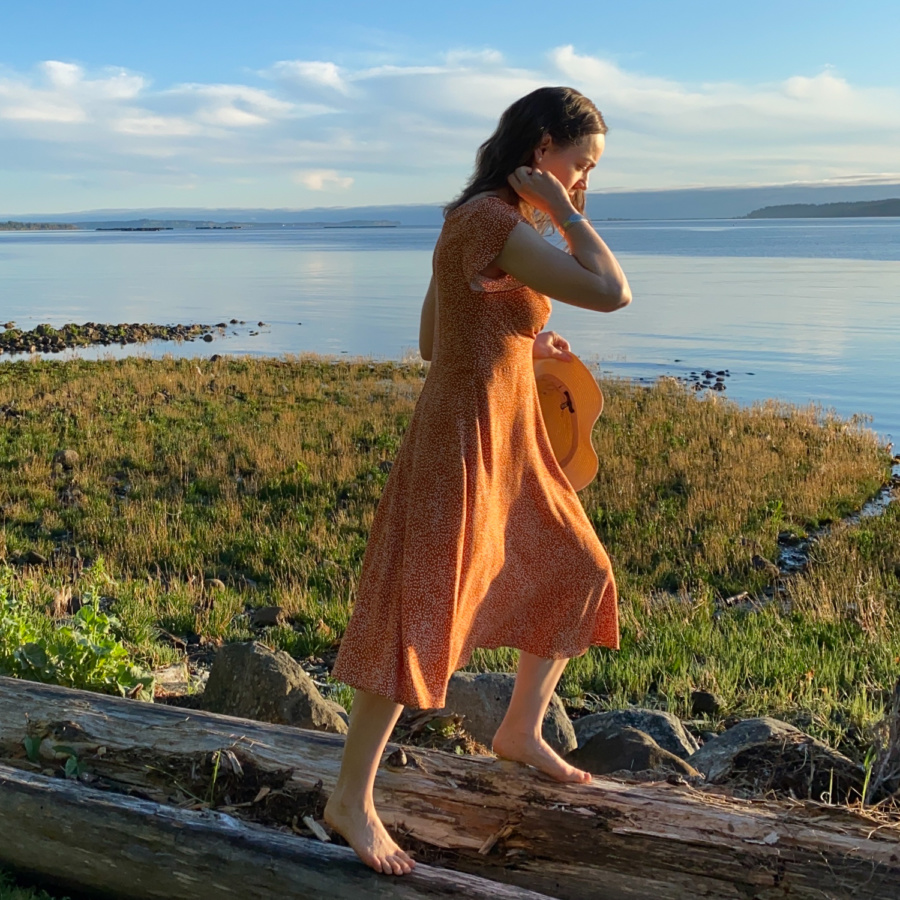 Me stepping onto a log on the beach with the water behind me, wearing a orange v-neck midi dress with white polka dots