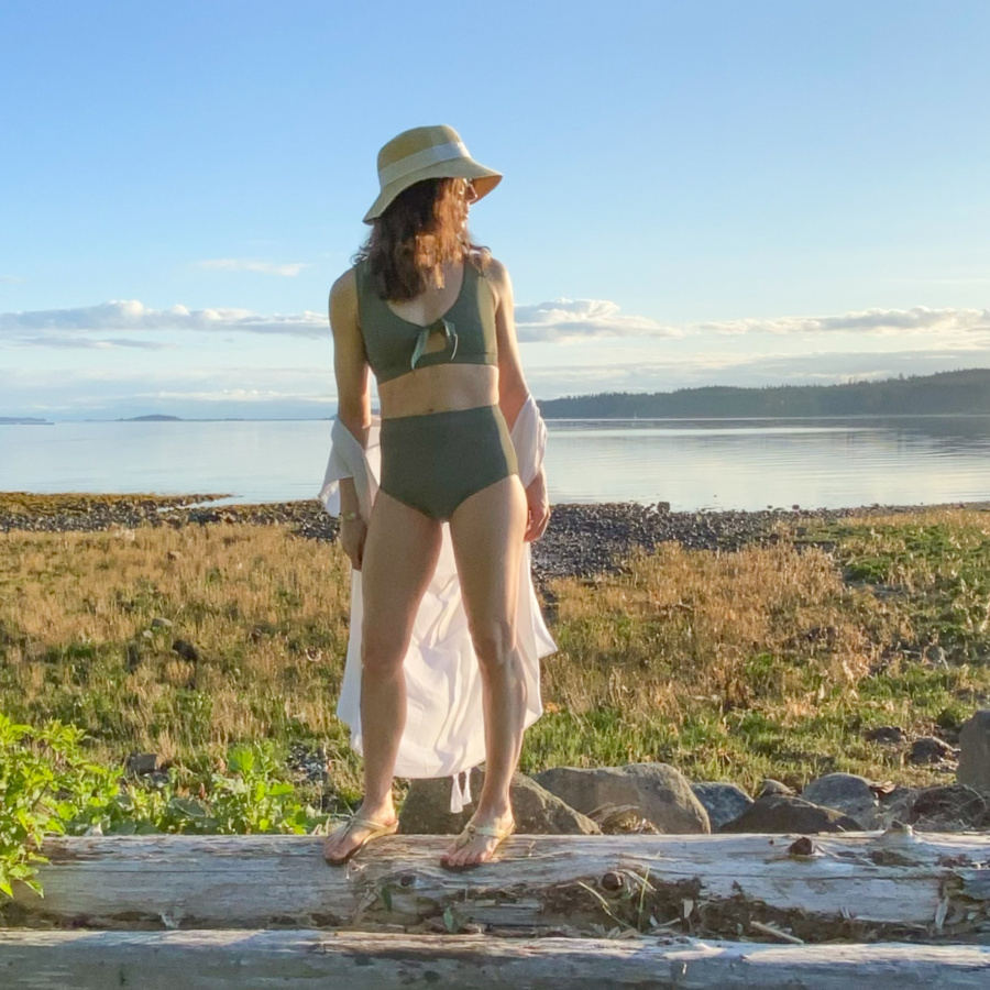 Me standing on a log in front of a rocky beach wearing a sage green swim suit and a hat