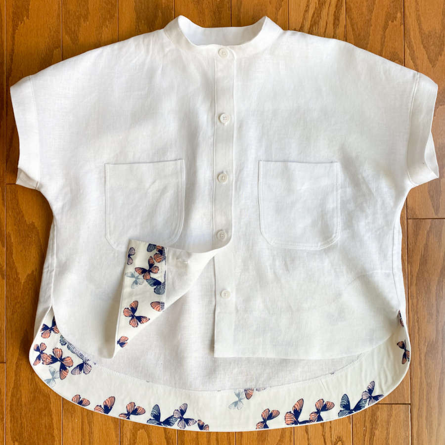 Buttoned white linen Kalle shirt lying on the floor with the butterfly-print facing showing