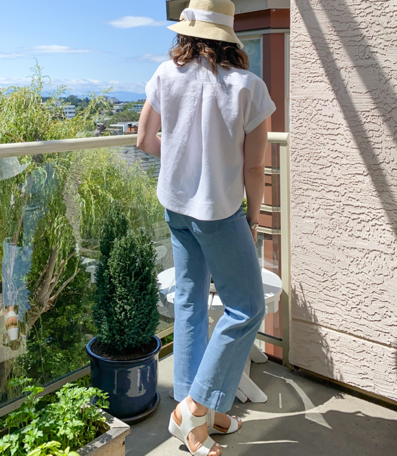 Me standing on a balcony wearing a cropped, white linen Kalle Shirt and blue jeans with my back to the camera.