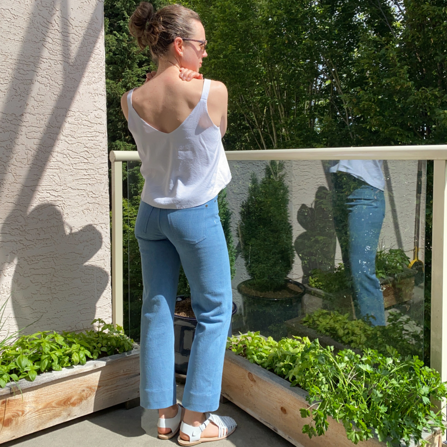 white modified Ogden cami and wide leg, light wash ginger jeans, back view
