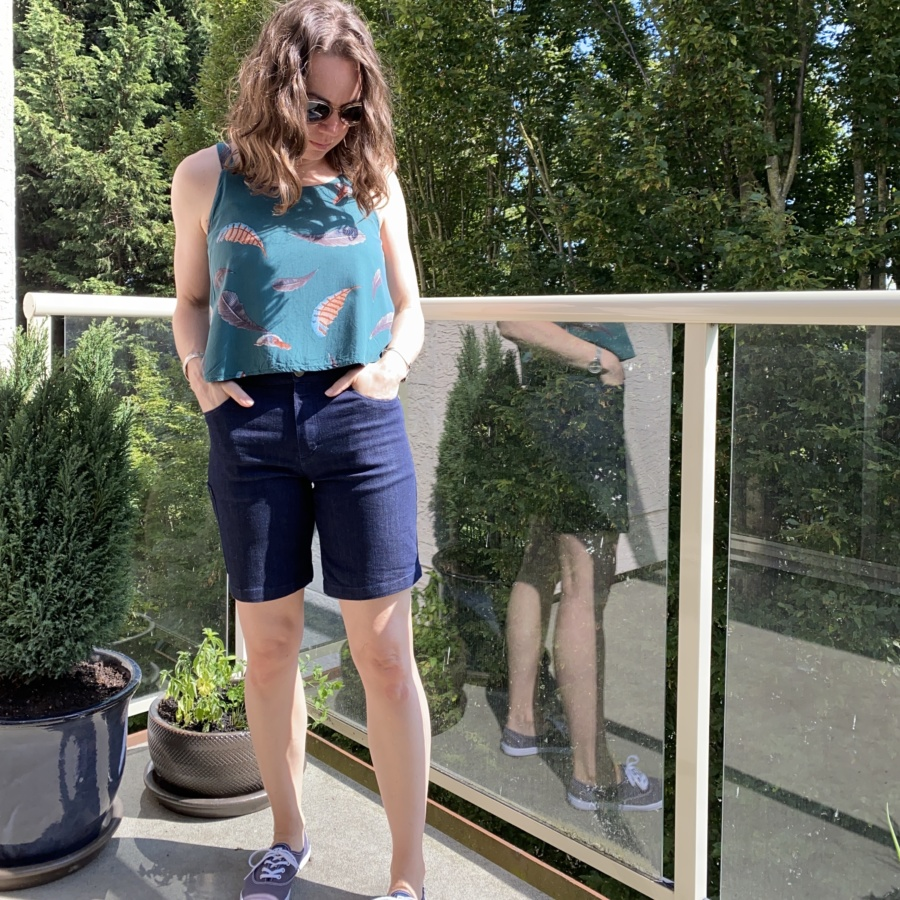 Me standing on a deck with my hands in my pockets wearing my new Ginger Jean shorts, a cropped, green ogden cami and navy blue keds