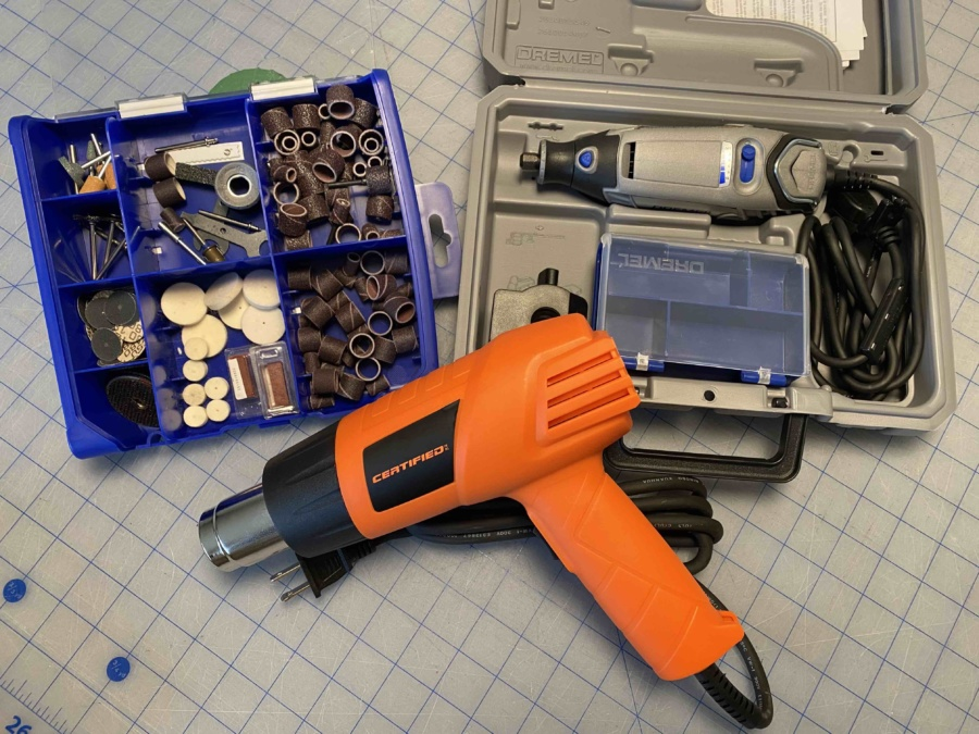 Dremel tool and accessories and an orange heat gun